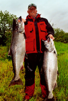 a man holds the two king/chinook salmon that he caught while fishing alaska's nushagak river with our guides