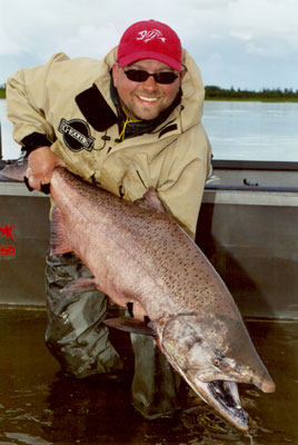 A fisherman holds the KIng/Chinook salmon he caught fishing Alaska's Nushagak River