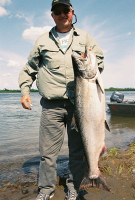 A fisherman holds his King/Chinook salmon on the bank of the Nushagak River