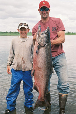 a young man with the king/chinook salmon that he caught with a guide on alaska's nushagak river at our lodge
